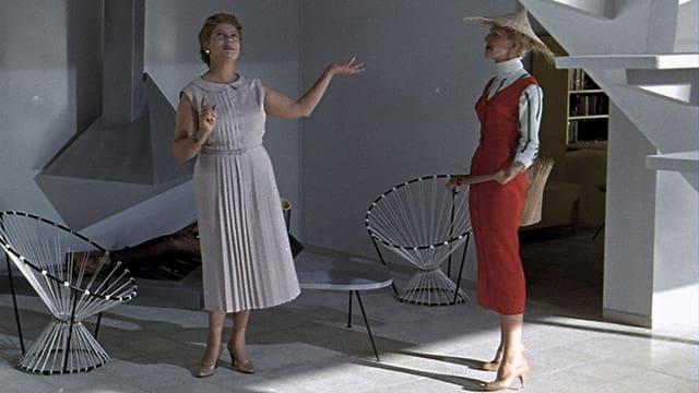 Zwei Damen stehen vor zwei mit Netzen bespannten Stühlen.