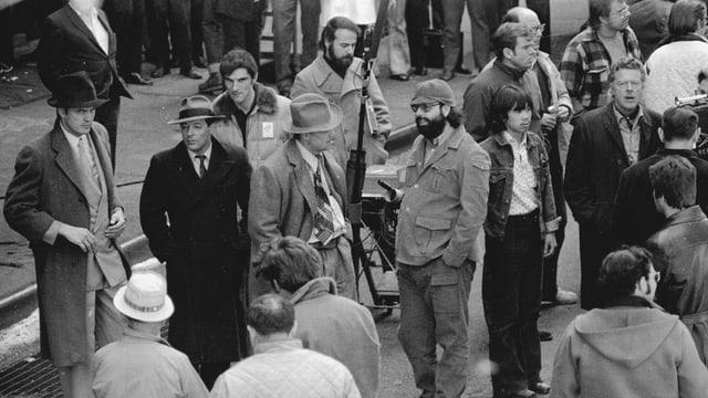 Menschen an der Arbeit am Set. Unter ihnen Marlon Brando und Francis Ford Coppola.