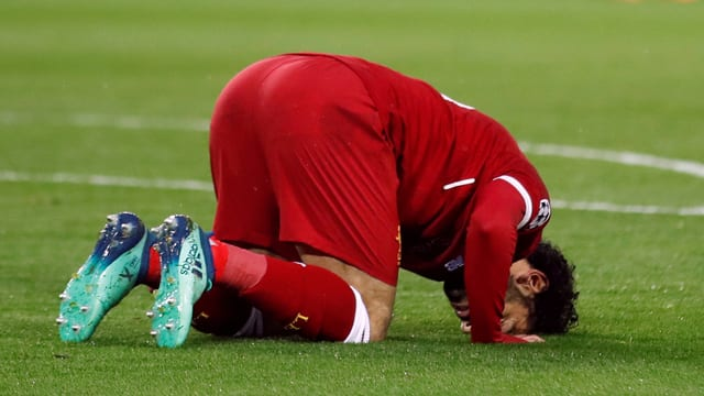 Ein Fussballspieler betet auf dem Rasen.