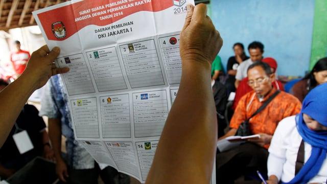 Ein Freiwilliger erklärt Wahlberechtigen den Wahlzettel