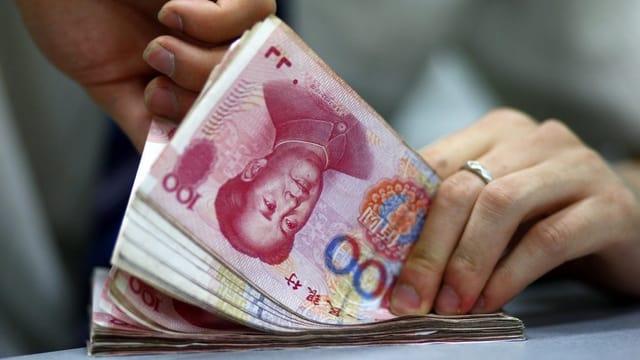 Hände, die chinesische Banknoten zählen.