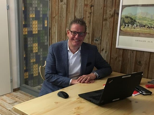 LeShop-Chef Dominiquw Locher sitzt an einem Holztisch in seinem Büro. Darauf steht ein Laptop
