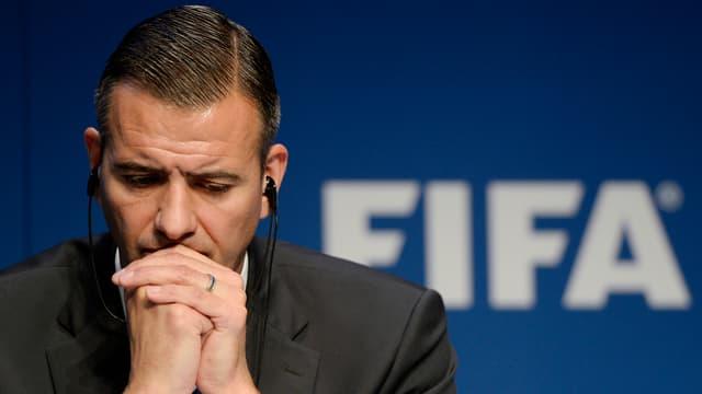 Markus Kattner stützt seinen Kopf auf zwei gefalteten Händen vor einem Fifa-Logo