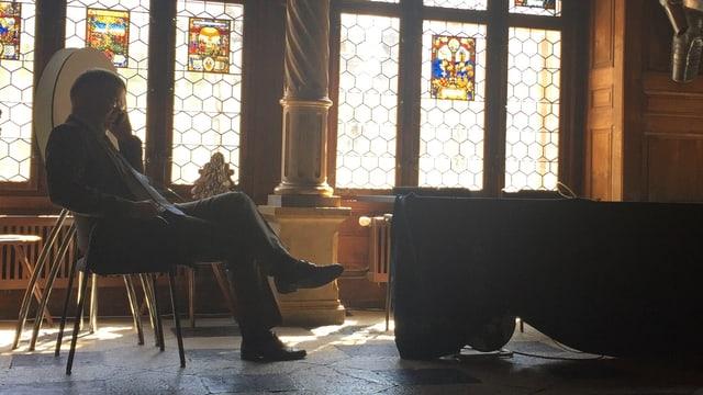 Scheuermeyer sitzt am Fenster auf einem Stuhl und telefoniert
