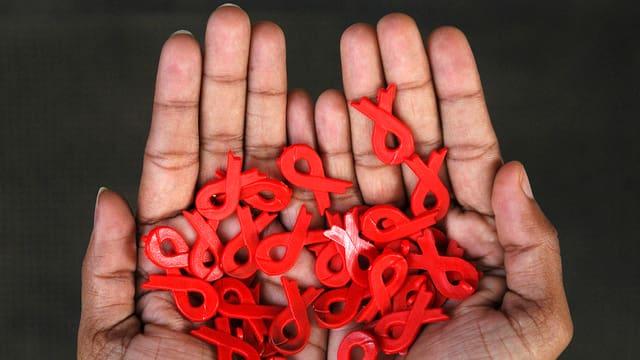 Mauns che tegnan bindels cotschens, il simbol per il cumbat cunter aids.
