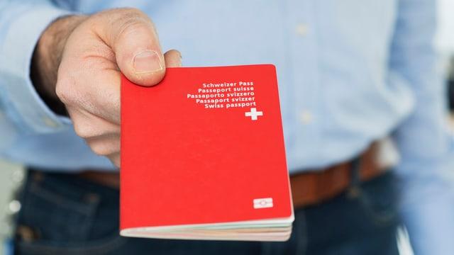 Eine Hand streckt einen Schweizer Pass hin.
