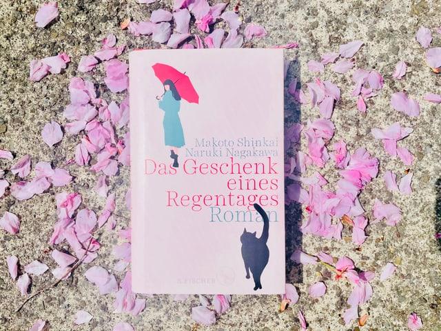 Der Roman «Das Geschenk eines Regentages» von Makoto Shinkai und Naruki Nagakawa liegt auf Kirschblüten