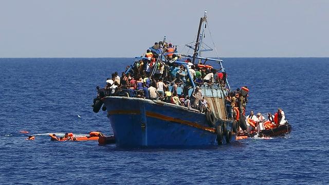 Flucht übers Mittelmeer von Libyen und Ägypten aus: Ein hoffnungslos überladenes Schiff mit rund 600 Menschen an Bord wird im August 2015 rund 16 Kilometer vor der libyschen Küste von Helfern aufgegriffen.