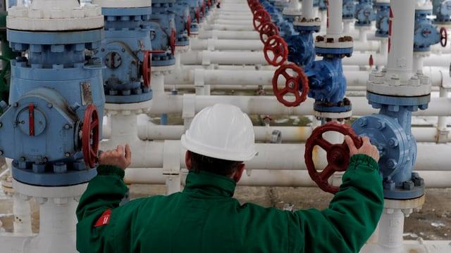 Arbeiter in grünem Overall schraubt an zwei von einer ganzen Reihe von Erdgasventilen.