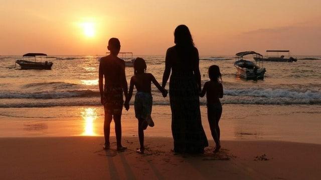 Eine Frau mit drei Kindern am Strand.