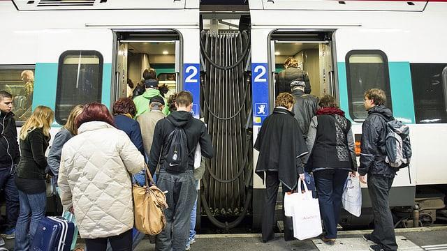 Menschen besteigen Zug.