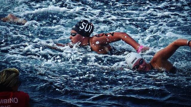 Wettkampf-Schwimmerinnen im wilden Gewässer, man sieht auch Schaum und Spritzer.
