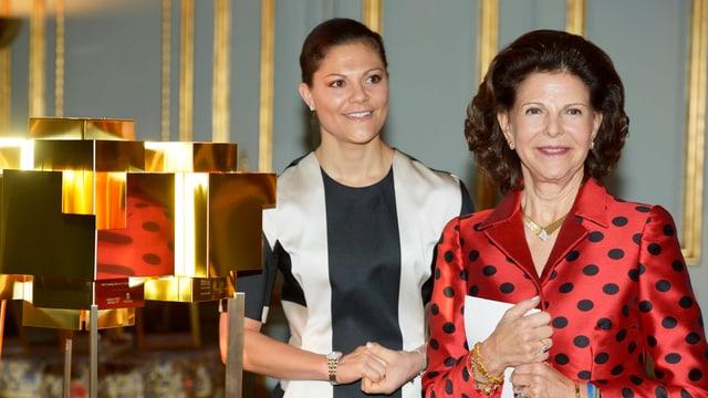 Kronprinzessin Victoria und Köngin Silvia stehen bei einer goldenen Skulptur und grinsen.