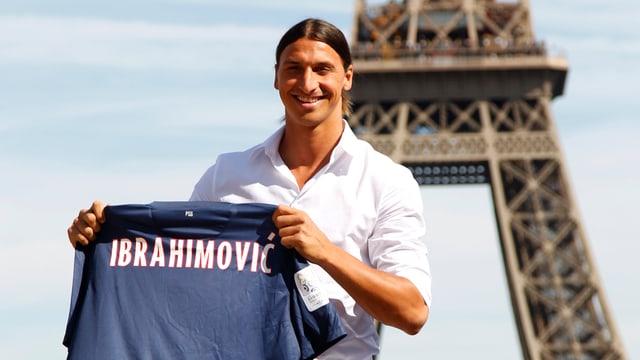 Zlatan Ibrahimovic bei seiner Verpflichtung für St. Germain vor dem Eiffelturm mit einem Trikot in den Händen.