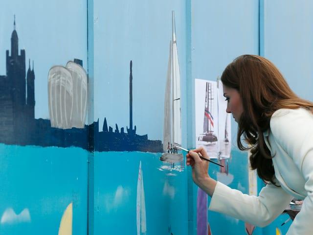 Herzogin Catherine in einem weissen Mantel malt ein Segelschiff auf eine Wand.