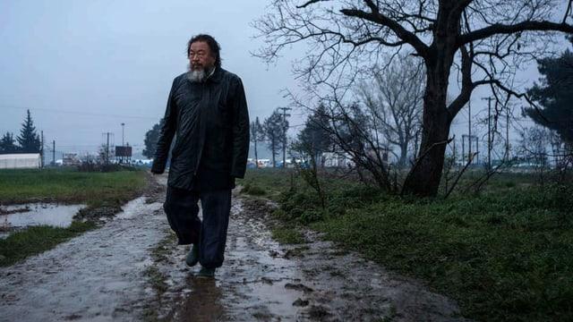 Ein Mann mit Bart geht in Socken über einen Weg.