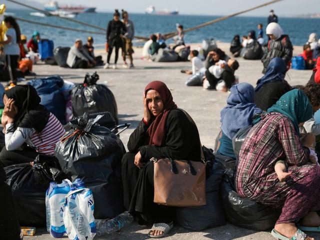 Frauen warten auf den Transfer aufs Festland