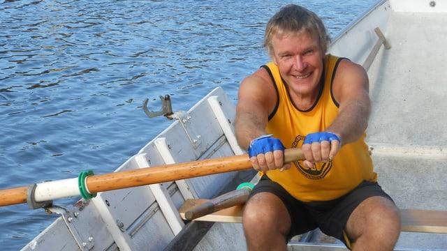 Jacques Thurneysen sitzt auf der Ruderbank eines Weidlings, rudert und lächelt in die Kamera.