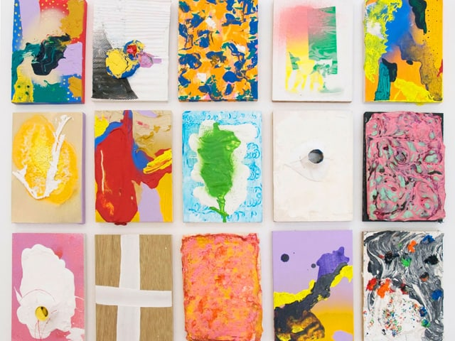 15 kleinere, farbige Bilder mit verschiedenen Motiven sind an einer weissen Wand zu einem einzigen grossen Bild angeordnet.