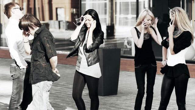 Fünf junge Leute stehen zusammen und telefonieren alle mit ihrem Handy.