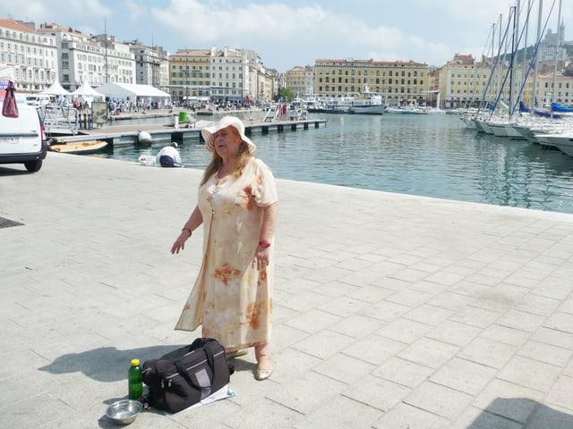 Eine Frau steht an einem Hafen und singt. Im Hintergrund sieht man Boote und Häuser von Marseille.