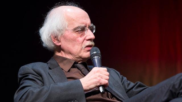Reinhard Schulze sitzend mit Mikrofon in der Hand.