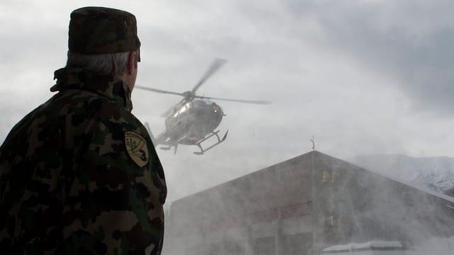 Soldat schaut einem Militärhelikopter bei der Landung zu.