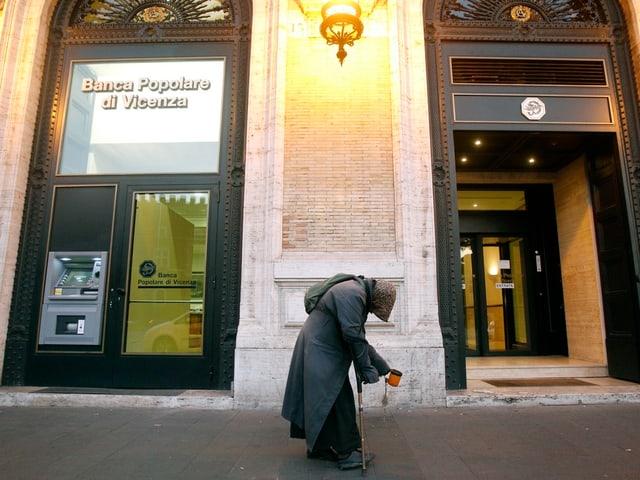 Ein Bettler vor einer Bank.