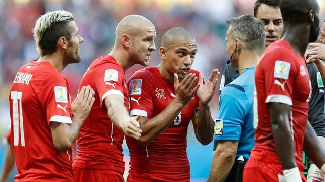 Valon Behrami, Philippe Senderos, Goekhan Inler und Diego Benaglio sind an der WM-Partie gegen Frankreich mit einem Entscheid unzufrieden und bestürmen Schiedsrichter Bjorn Kuipers.
