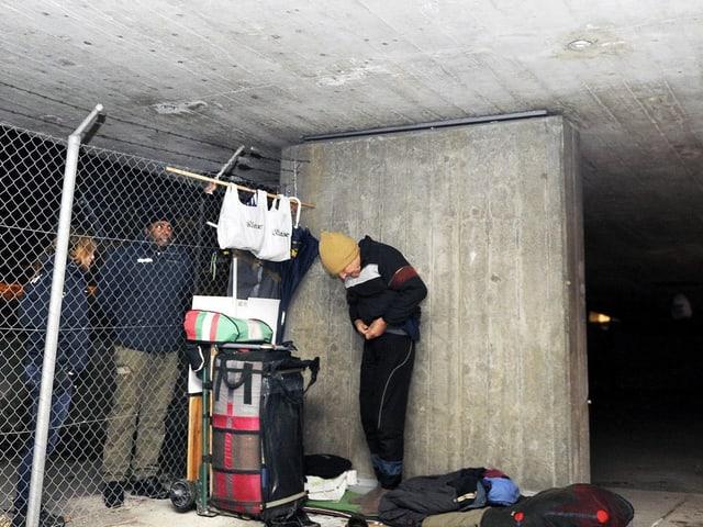Ein Mann bereitet neben Angehörigen der SIP (Sicherheit, Intervention, Prävention, Stadt Zürich) seine Schlafstätte vor unter einer Brücke in Zürich.