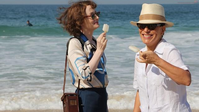 Zwei Frauen stehen am Strand und essen Eis am Stiel.