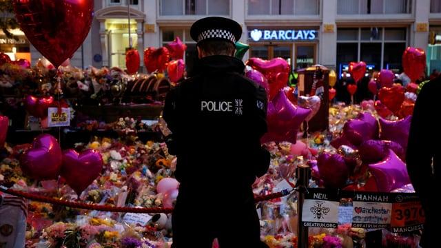 Polizist vor Blumen in Manchester.
