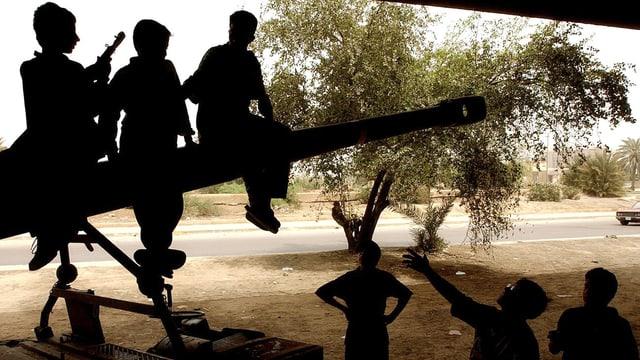 Drei Kinder sitzen auf einer Kanone, einer trägt eine Waffe. Von unten rufen ihnen andere Kinder zu.