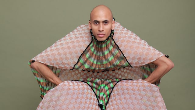 Ein Mann in einem auffälligen Gewand posiert vor der Kamera.