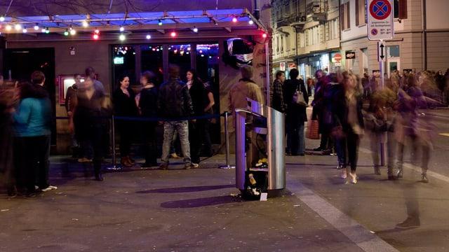 Menschenmenge vor einer Bar an der Zürcher Langstrasse bei Nacht.