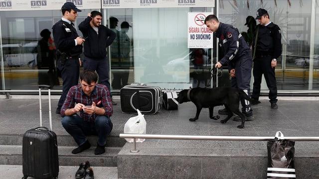 Polizisten mit Spürhund, davor sitzt ein Mann auf dem Trottoir