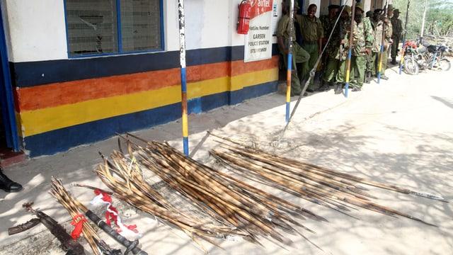 Auf dem Boden liegen Waffen, im Hintergrund warten Männer in Militäruniform.