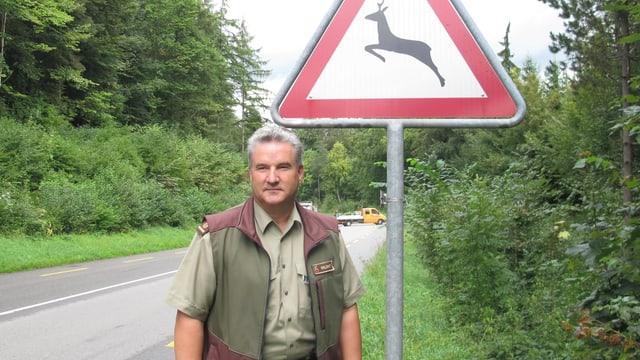 Ein Mann steht an einer Strassen vor einem Schild.