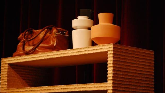 Tasche und Vasen auf Möbelstück aus Holz.