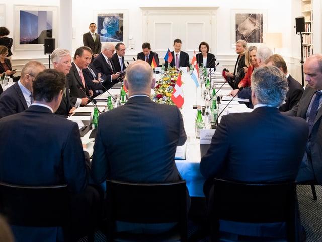 Die Teilnehmer der Konferenz sitzen an einem Tisch.