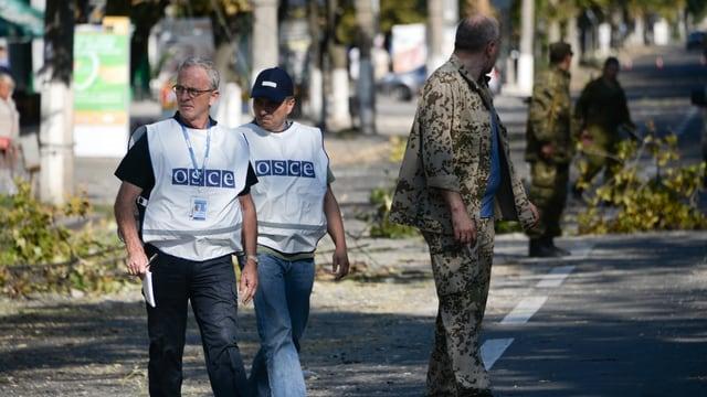 Zwei OSZE-Mitarbeiter überqueren eine Strasse.