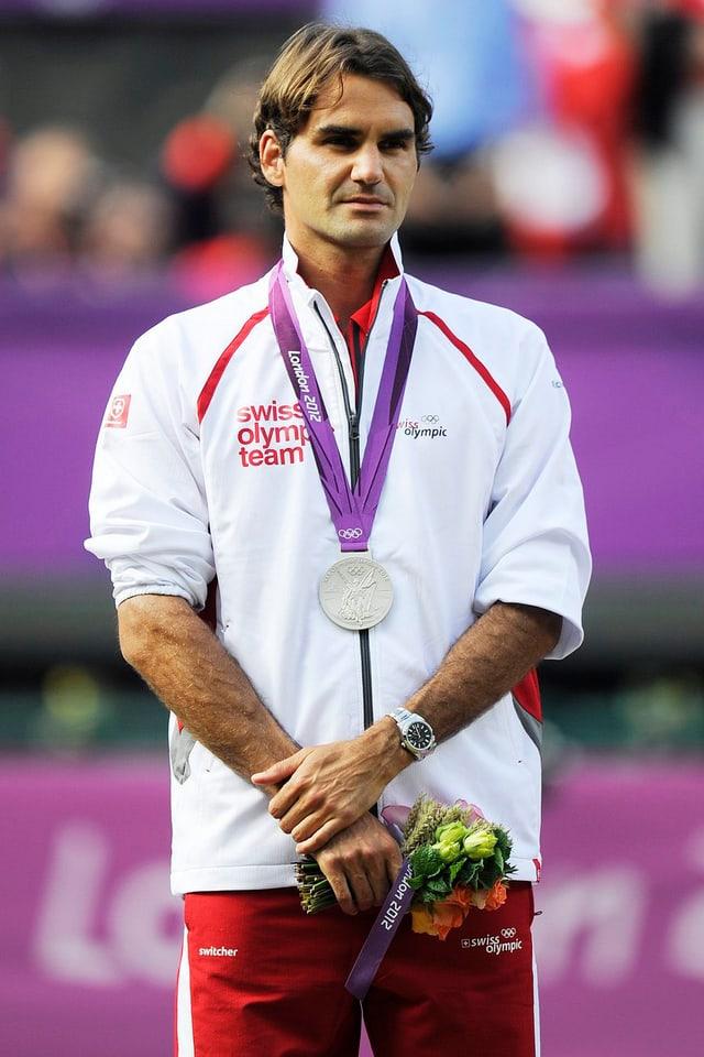 Roger Federer posiert an den Olympischen Spielen mit seiner Silbermedaille.