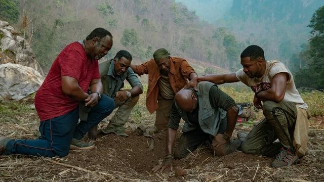 Die fünf Hauptfiguren von «Da 5 Bloods» knien nieder, als sie das Grab ihres Kollegen entdecken.