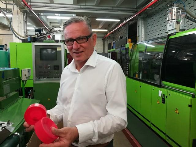 Mann hält rote Plastik-Teile in der Hand. Grüne Maschinen im Hintergrund.
