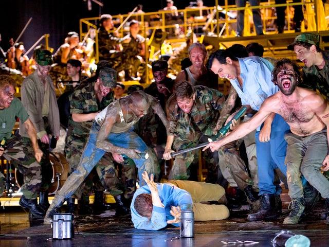 Eine Horde Männer in Uniform schlagen auf einen Mann in Strassenkleidung ein, ein Betrunkener lacht.