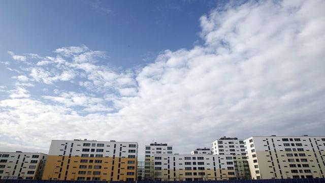 Wohnüberbauung vor Himmel mit Wolken.