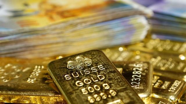 Goldbarren und Frankenscheine.