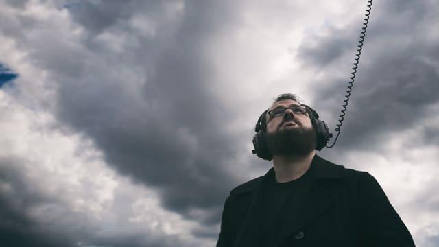 Blick von unten auf einen Mann mit einem grossen Kopfhörer. Das Kabel des Kopfhörers geht nach oben Richtung Himmel