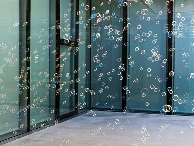 In einem Innenhof mit grünen Fenstern sind Seifenblasen in verschiedenen Farben zu sehen.