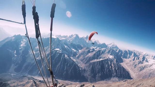 Gleitschirmflieger über den verschneiten Bergen